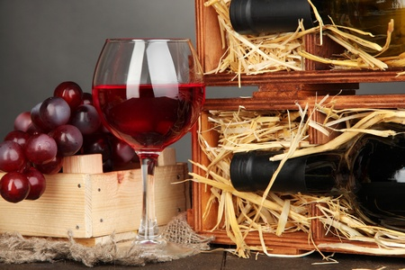 cabarnet: Wooden case with wine bottles, wineglass and grape on grey background