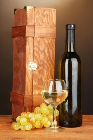 Wooden case with wine bottle on wooden table on brown background Stock Photo - 17264541