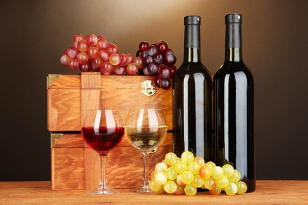 Wooden cases with wine bottles on wooden table on brown background Stock Photo - 17264556