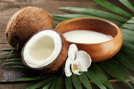 noix de coco: De noix de coco avec des feuilles et des fleurs, sur fond de bois gris