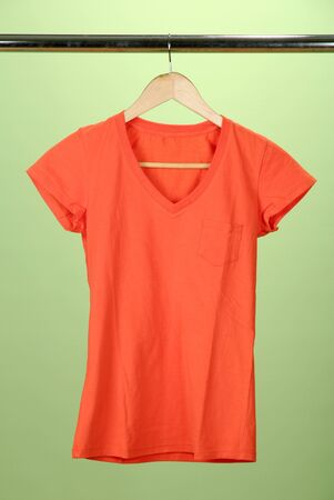 clothing rack: T-shirt on wooden hanger, on green background Stock Photo