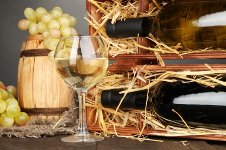 Wooden case with wine bottles, barrel, wineglass and grape on wooden table on grey background photo