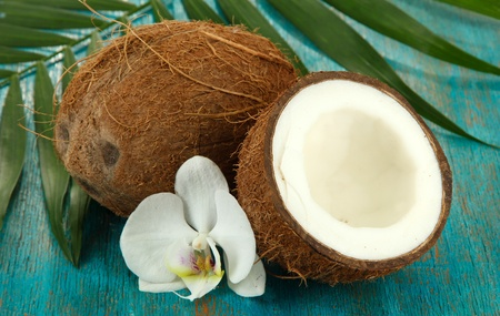 Coconuts with leaves and flower, on blue wooden background Stock Photo - 17265876