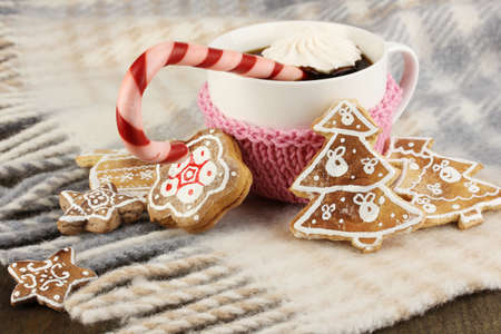 Cup of coffee with Christmas sweetness on plaid close-up photo