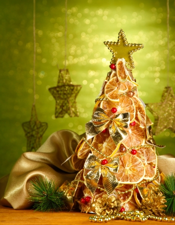 beautiful christmas tree of dry lemons with decor, on shine green background photo