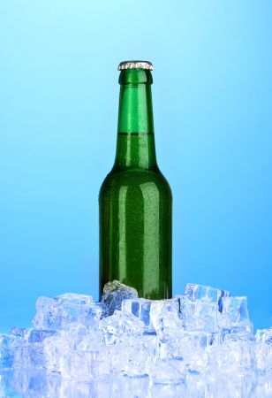 Beer bottle in ice on blue background Stock Photo - 17265669