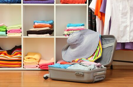 Open silver suitcase with clothing in room Stock Photo - 17265818