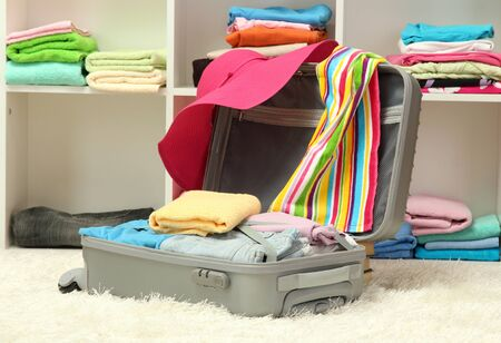Open silver suitcase with clothing in room Stock Photo - 17265740