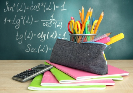 pencil case: Back to school - blackboard with pencil-box and school equipment on table Stock Photo