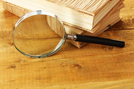 Magnifying glass and books on table photo