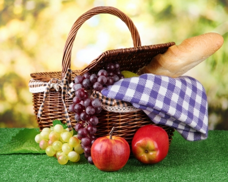 Picnic basket and bottle of wine on grass on bright background photo