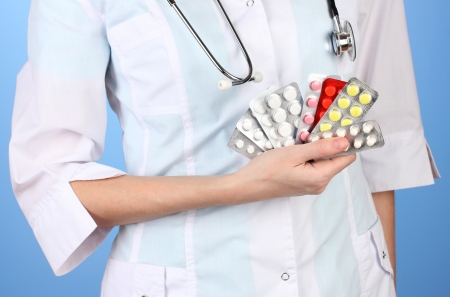 Close-up of female doctor hand holding pills, on color background photo
