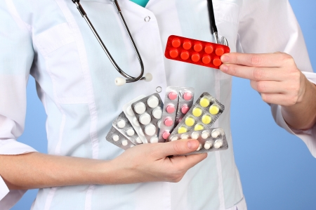 Close-up of female doctor hand holding pills, on color background Stock Photo - 17265737