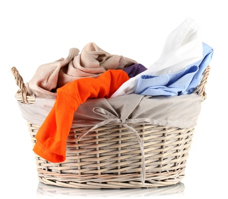 dirty clothes: Bright clothes in laundry basket, isolated on white