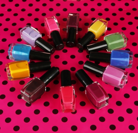 bright nail polishes on table on black background photo