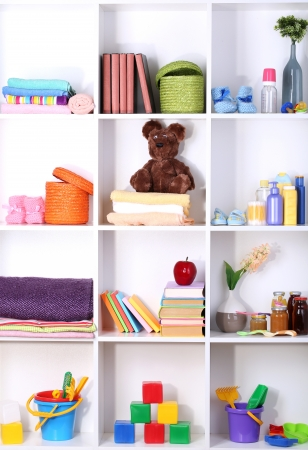multiple objects: Beautiful white shelves with different baby related objects