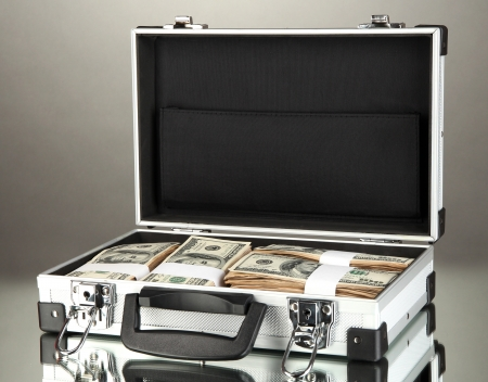 Suitcase with 100 dollar bills on grey background Stock Photo - 17265778