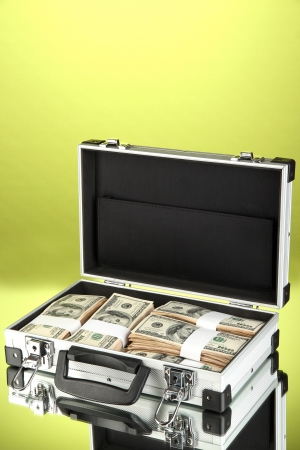 Suitcase with 100 dollar bills on green background Stock Photo - 17265768