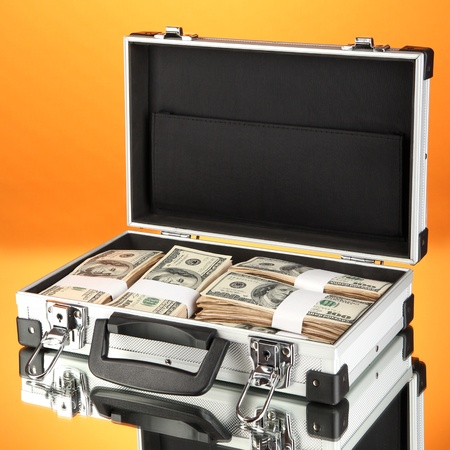 Suitcase with 100 dollar bills on orange background Stock Photo - 17265902