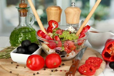 Fresh greek salad in glass bowl surrounded by ingredients for cooking on wooden table on window background Stock Photo - 17321752