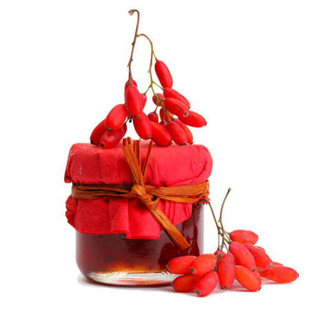 ripe barberries and jar of jam isolated white photo