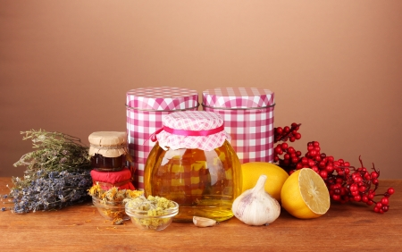 Honey and others natural medicine for winter flue, on wooden table on brown background photo