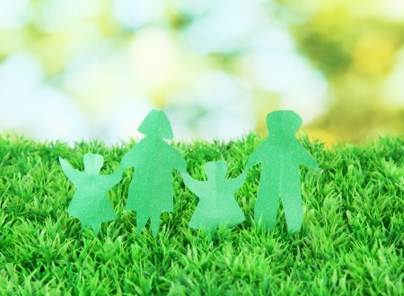 Paper people on green grass on bright background Stock Photo - 17321623