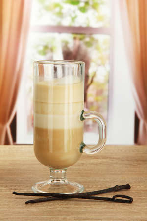 Fragrant coffee latte in glass cup with vanilla pods, on table in cafe photo