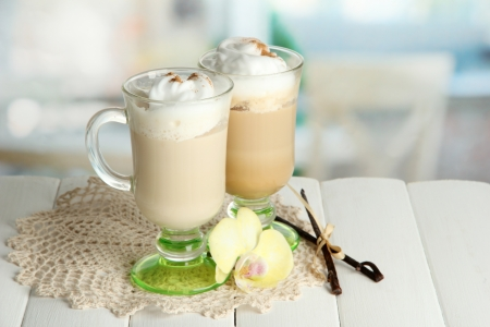 fragrant: Fragrant coffee latte in glasses cups with spices, on wooden table