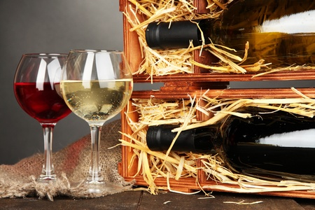 Wooden case with wine bottles and wineglasses on grey background photo