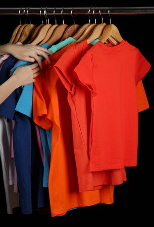 clothing rack: Variety of casual shirts on wooden hangers, isolated on black