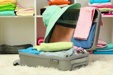Open silver suitcase with clothing in room Stock Photo - 17321767