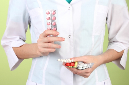 Close-up of female doctor hand holding pills, on color background Stock Photo - 17332322