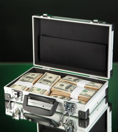 Suitcase with 100 dollar bills on dark color background Stock Photo - 17332503
