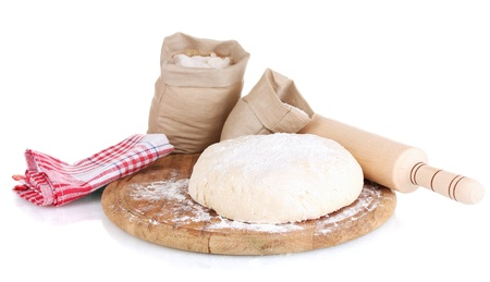 Dough and bags with flour on wooden board isolated on white photo