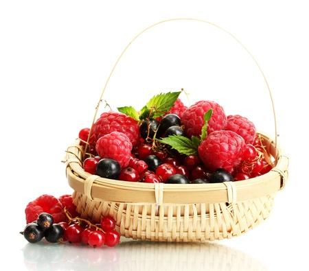 cesta de frutas: bayas maduras con menta en la cesta aislada en blanco