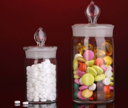 Capsules and pills in receptacles on red background photo