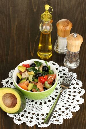 Tasty avocado salad in bowl   surrounded by spices on wooden table close-up photo