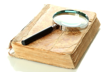 Magnifying glass and book isolated on white photo
