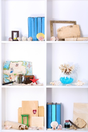 Beautiful white shelves with different travel related objects photo