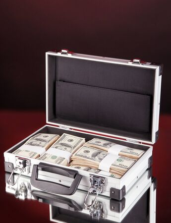 Suitcase with 100 dollar bills on dark color background photo