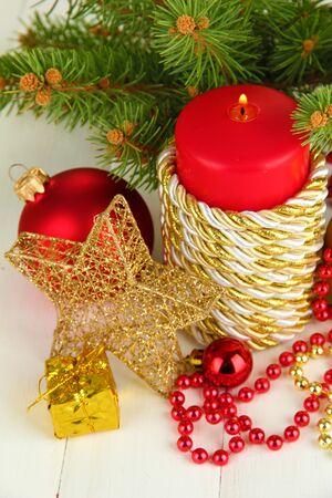 velas de navidad: Vela roja con la decoraci?n de Navidad sobre fondo claro