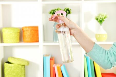 Sprayed air freshener in hand on white shelves background Stock Photo - 17399975