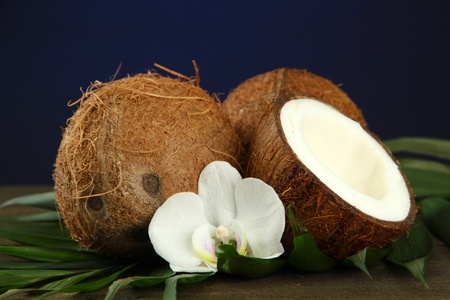 Coconuts with leaves and flower, on wooden table on blue background Stock Photo - 17400851