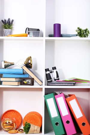 home related: Beautiful white shelves with scattered different home related objects Stock Photo
