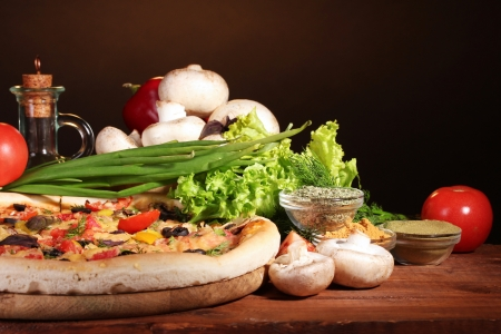 pizzeria: delicious pizza, vegetables and spices on wooden table on brown background