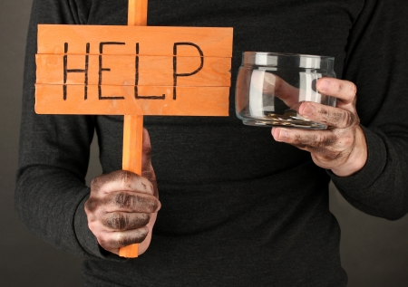 wastrel: homeless man asks for help, on black background close-up Stock Photo
