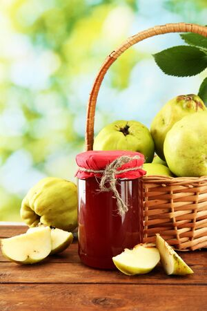 jar of jam and quinces with leaves in basket, on green background Stock Photo - 17403990