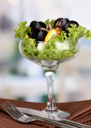 Snack of mussels and lemon on vase on wooden table on room background photo