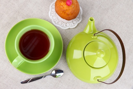 Top view of cup of tea and teapot on tablecloths photo